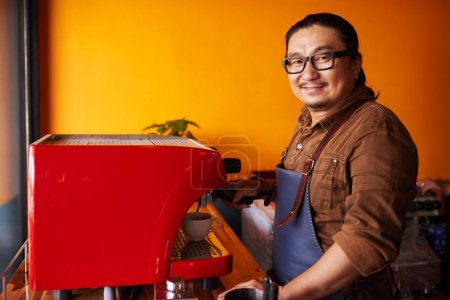 Portrait of coffee shop owner making cup of espresso