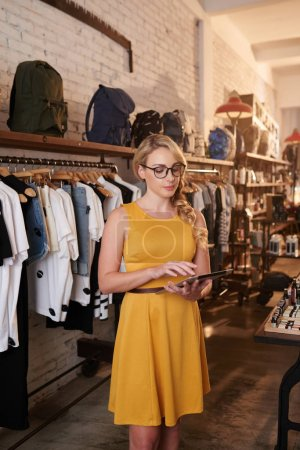 beautiful blonde woman in clothes shop using digital tablet