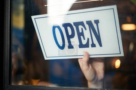 Photo for Close up shot of person hand opening door with board - Royalty Free Image