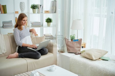 Young woman sitting on sofa and working on laptop in living room
