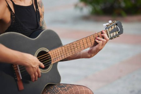 Close-up image of woman playing guitar outdoors