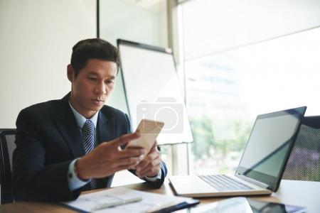 Serious Vietnamese businessman sitting at workplace and reading message on his smartphone