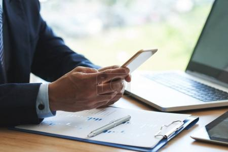 Close-up image of business executive using application on smartphone