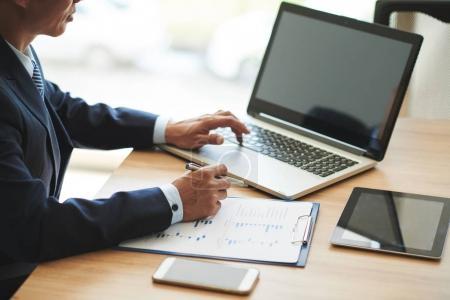 Geschäftsmann nutzt Laptop und arbeitet an Finanzbericht