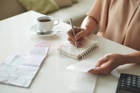 Close-up image of housewife writing down all her expenses for the last month