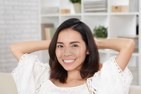 smiling beautiful asian young woman relaxing on sofa at cozy home
