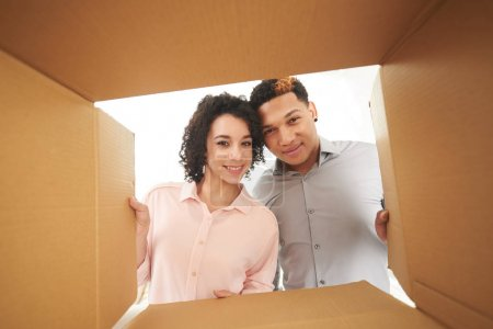 Young smiling couple looking into opened cardboard box