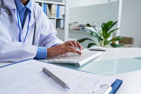 Hands of female doctor typing on keyboard