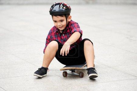 Joyful mixed-race boy in helmet sitting on skateboard