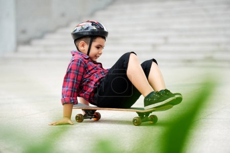 Cheerful preschool boy sitting on skateboard and trying to ride