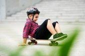 Cheerful preschool boy sitting on skateboard and trying to ride