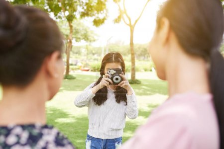 Girl taking photos of her hugging mother and grandmother in the park