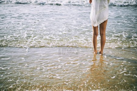 Photo pour Vue arrière de la fille aux pieds nus, debout dans la mer - image libre de droit