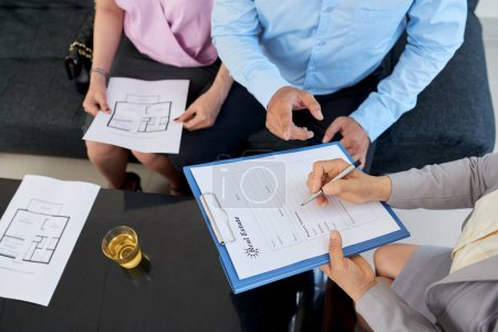 Photo for Estate broker filling contract for couple, view from above - Royalty Free Image