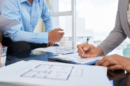 Hands of broker writing down every wish of her client