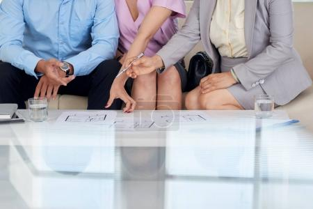 Cropped image of clients and estate broker examining house blueprint on table