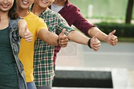 Cropped image of smiling people showing thumbs-up