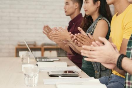 Young people clapping to the speaker at business meeting