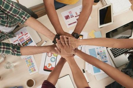 Photo pour Équipe de développeurs d'applications mobiles empilant les mains avant le travail - image libre de droit