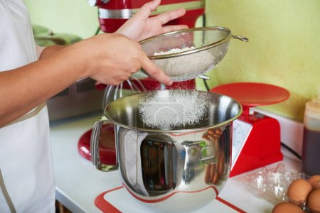 Photo for Hands of baker sifting flour into mixer bowl - Royalty Free Image