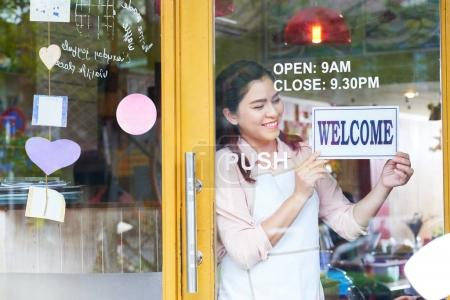 Smiling young bakery owner hanging welcome sign on the door
