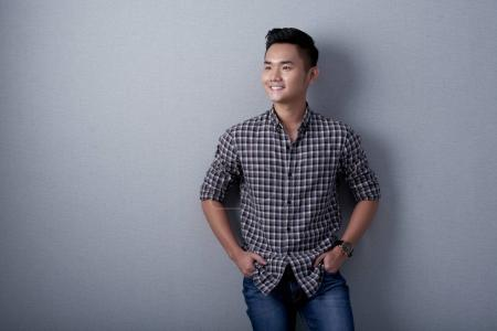 Portrait of smiling asian man with hands in pockets leaning on gray wall