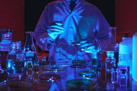 Cropped image of scientist conducting experiment in dark laboratory