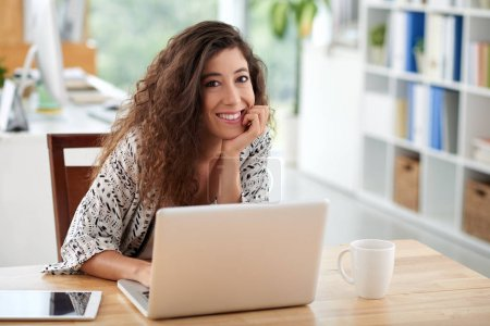 Waist-up portrait of pretty young businesswoman looking at camera with wide smile while working on laptop in spacious office