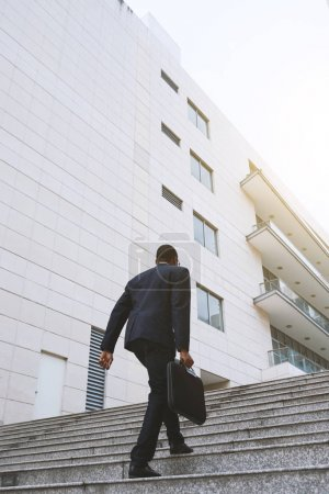 Businessman going to the office building, view from below