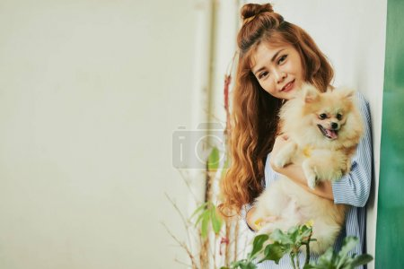 Portrait of pretty Vietnamese young woman carrying her Pomeranian spitz