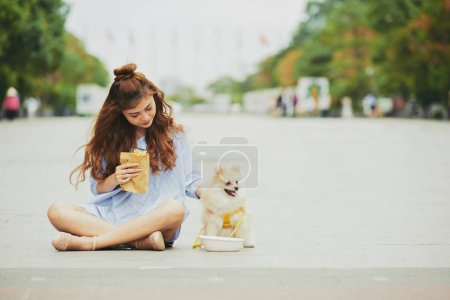 Pretty young woman and her dog sitting outdoors and having snacks