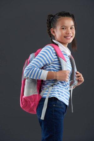 Photo pour Portrait de joyeux asiatique écolière sur fond gris - image libre de droit