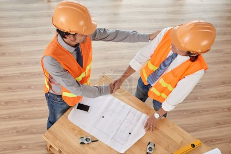 Engineer tapping on shoulder and shaking hand of his colleague, view from above