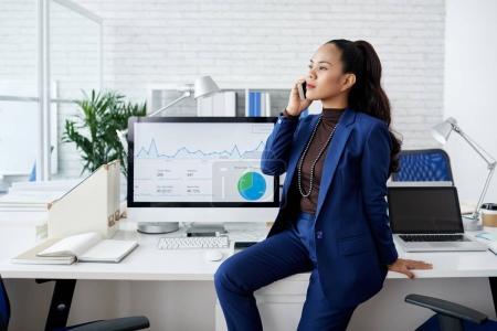 attraktive asiatische Geschäftsfrau sitzt auf ihrem Tisch und telefoniert