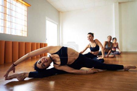 smiling women stretching in dancing studio