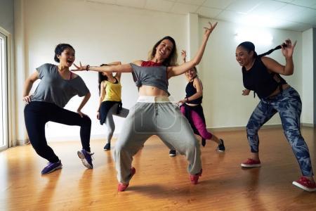dynamic women practicing hip hop dance choreography in dancing studio