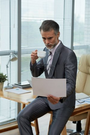 Mature business executive drinking cup of coffee when analyzing financial report