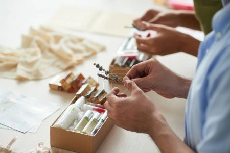 People filling boxes with organic cosmetics and handmade soap to sell it online