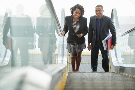 Cheerful African-American business executives with documents standing in the beginning of escalator