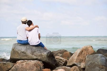 Hugging friends sitting on the rock by the water