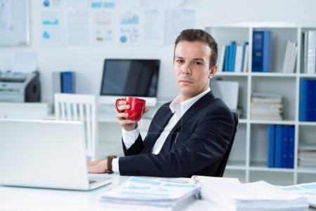 Portrait of handsome young businessman with a cup of coffee