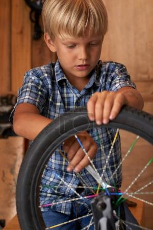 Boy checking if the bicycle wheel is secure