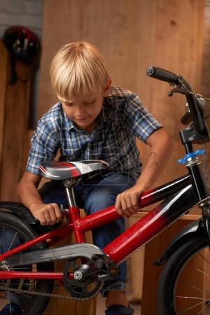 Boy adjusting seat of his bicycle in garage