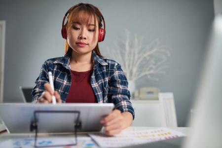 Concentrated young photo editor listening to music in headphones while using graphics tablet