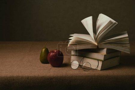 Photo pour Nature morte : livre ouvert, verres et fruits sur la table - image libre de droit