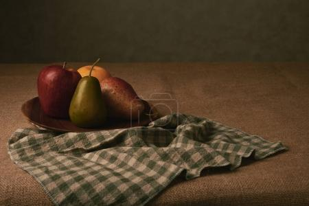 Various fresh ripe fruits in plate on table