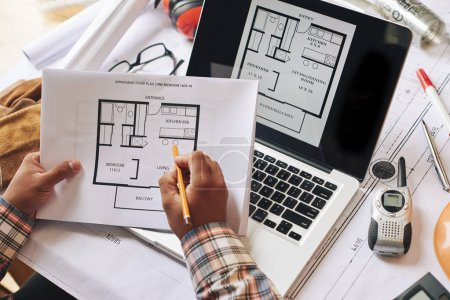 Hands of architect taking notes on apartment plan