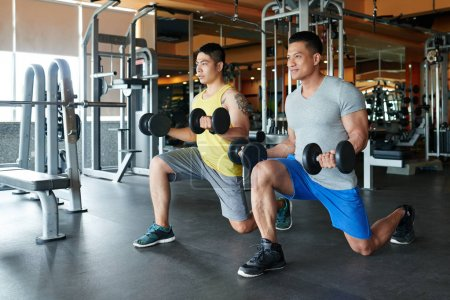 Fit sporty two Asian men doing lunges with dumbbells