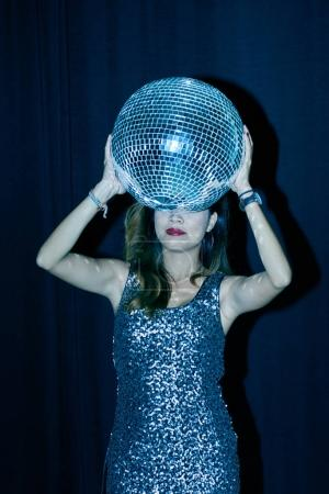 Young woman with disco ball dancing in night club