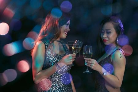 Pretty Vietnamese women drinking white wine at party in night club